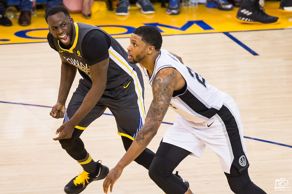 Golden State Warriors forward Draymond Green (23) reacts to being knocked down by San Antonio Spurs forward Rudy Gay (22) during Game 2 of the Western Conference Quarterfinals at Oracle Arena in Oakland, Calif., on April 16, 2018. (Stan Olszewski/Special to S.F. Examiner)