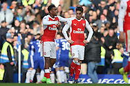 Alex Iwobi of Arsenal puts his arms around Mesut Ozil of Arsenal after Eden Hazard of Chelsea scores a goal. Premier league match, Chelsea v Arsenal at Stamford Bridge in London on Saturday 4th February 2017.<br /> pic by John Patrick Fletcher, Andrew Orchard sports photography.