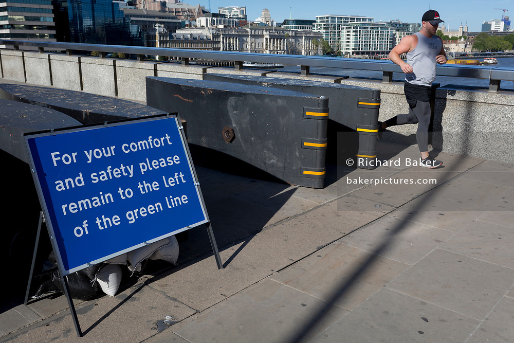 With the UK death toll reaching 38,161, a further 324 victims in the last 24hrs, and the government's pandemic lockdown still in effect, mainly walkers, runners and sightseers now cross at what would normally be rush-hour on London Bridge, which has quickly been converted to a social distancing thoroughfare over the river Thames where pedestrians should keep to the left of a green centreline, on 29th May 2020, in London, England.
