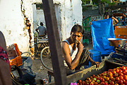 A tomato seller at rest at his stall in a market in Nizammuddin West, New Delhi, India.