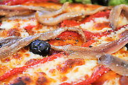 Anchovies and black olives on a Pizza