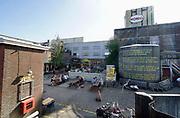 Nederland, Nijmegen,19-7-2020 Het vroegere fabriekscomplex van de Honig fabriek. Het Honigcomplex is een tijdelijk bedrijfsverzamelgebouw gevestigd in de voormalige Honigfabriek in Nijmegen. Het gebouw huisvest 150 culturele en ambachtelijke bedrijfjes. Het complex met de beeldbepalende meelsilo en het bekende logo staat op de nominatie om in 2022 te worden gesloopt ten behoeve van woningbouw. Het oudste deel en de silo worden behouden . . De gemeente wilde het fabrieksterrein gebruiken voor woningbouw, nieuwbouw woningen. Door de kredietcrisis en de crisis op de woningmarkt is dit plan in 2012 uitgesteld en is het voor een aantal jaren aangewezen als een broedplaats en smeltkroes voor culturele en creatieve activiteiten en ondernemingen waaronder galerie Bart, muziekcafe Brebl . Ook horeca zoals restaurant de Meesterproef en bierbrouwer Oersoep . De nieuwe waalbrug, brug over de Waal De Oversteek ligt hier vlakbij . Foto: Flip Franssen