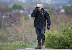 © Licensed to London News Pictures. 04/05/2021. London, UK. An elderly man clings on to his hat in strong winds on Hampstead Heath in North London. High winds and heavy rain are affecting parts of the UK today. Photo credit: Ben Cawthra/LNP