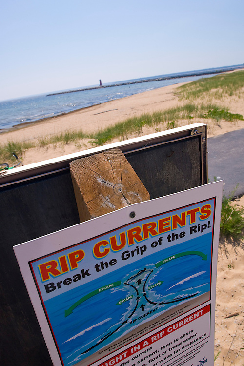 A sign warns of rip currents or rip tides at a Lake Michigan beach in Manistique Michigan.