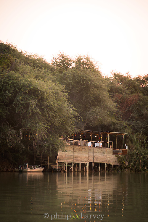 Seera Cafema Camp seen from the water, boat moored outside, Kunene River, Hartmanns Valley, Northern Namibia, Southern Africa
