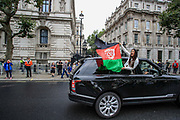 """Afghan woman carries the Afghan national flag during a protest """"Save Afghanistan"""" to protest the resurgence of the Taliban outside Downing Street, Britain's PM Office in central London on Saturday, Aug 21, 2021. (VX Photo/ Vudi Xhymshiti)"""