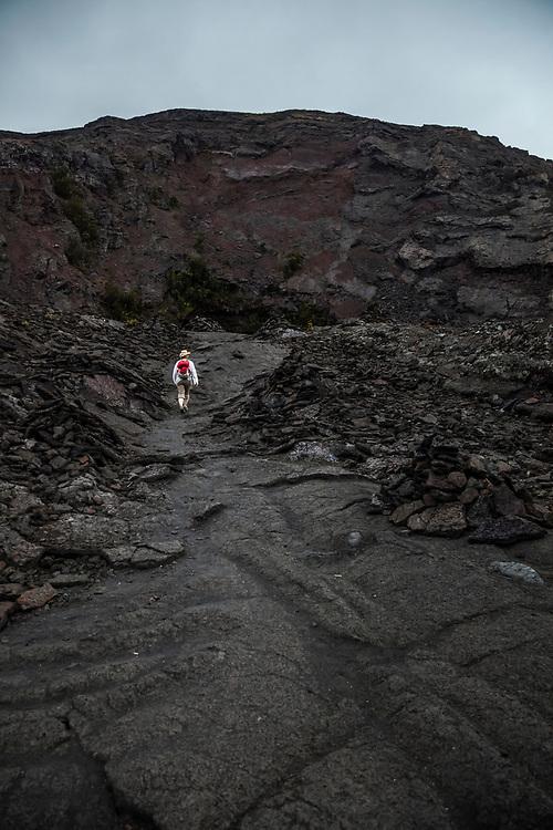 A woman walks toward Pu'u Pua'i or the Gushing Hill, a volcanic feature in Hawaii Volcanoes National Park, Hawai'i, USA