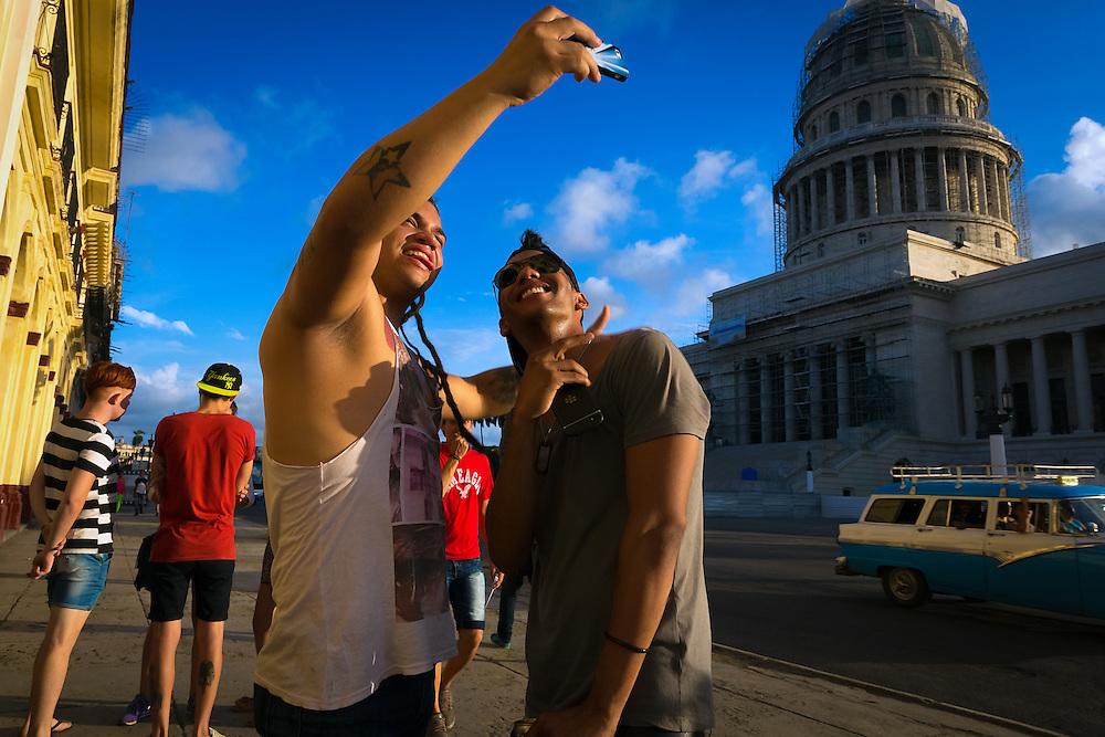 Marlon Marrero, left, and Rolando Labarrare take a selfie near the National Capitol Building in Old Havana. (David Albers/Staff)