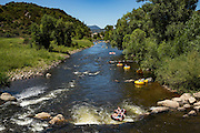 People raft using tubes down the Yampa River on a summer day in Steamboat Springs, Colorado.