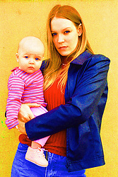Young teenage mother standing outside holding baby daughter,
