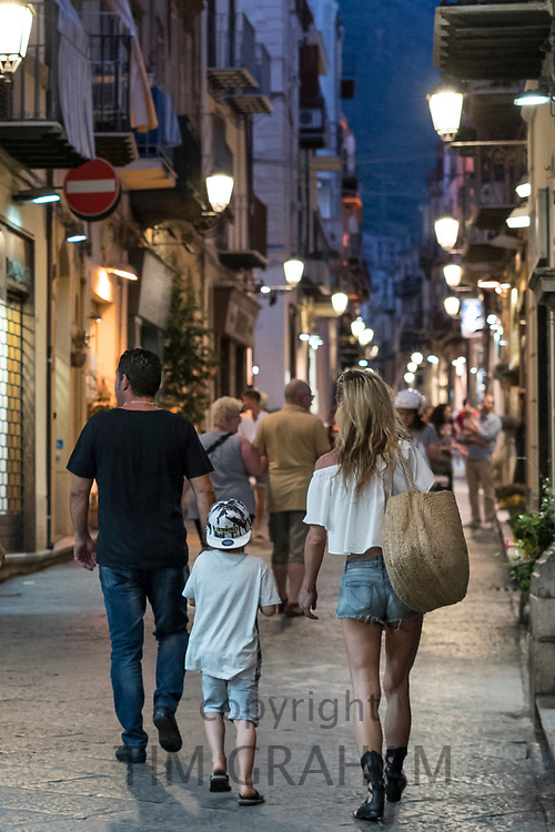 Tourists, family group, in street scene in town of Cefalu in Northern Sicily, Italy