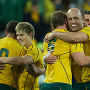 Nathan Sharpe, Australia, (far right), embraces Rocky Elsom as Quade Cooper (left) embraces James O' Connor, after Australia's victory  during the South Africa V Australia Quarter Final match at the IRB Rugby World Cup tournament. Wellington Regional Stadium, Wellington, New Zealand, 9th October 2011. Photo Tim Clayton...