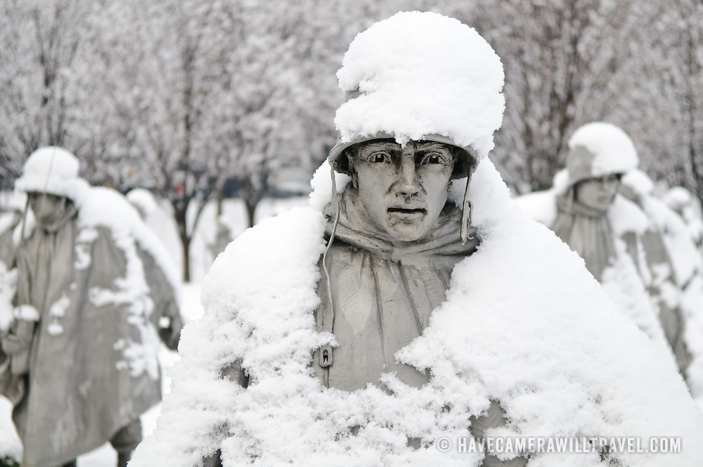 """A statue of a soldier at the Korean War Veterans Memorial on the National Mall on a snowy winter morning. The Korean War Veterans Memorial, unveiled in 1992, sits on the northwestern end of the National Mall, not far from the Lincoln Memorial. It consists of several elements designed by different people and groups. It has a triangular footprint with the main elements being """"The Column"""" consisting of 19 stainless steel solders, each over 7 feet tall, and a reflective granite wall etched with the faces of thousands of Americans who lost their lives in the war. At one end of the triangle, behind the soldiers, is a grove of trees. At the other is a large American flag and a small Pool of Remembrance. Among the designers were Frank Gaylord (the soldiers) and Louis Nelson (the reflecting granite wall)."""