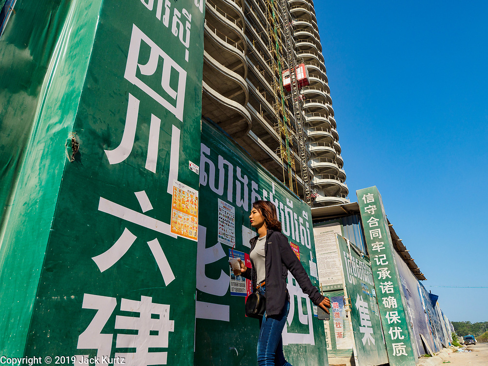 """15 FEBRUARY 2019 - SIHANOUKVILLE, CAMBODIA:  A Cambodian woman goes into the Blue Bay casino and resort construction site in Sihanoukville. There are about 80 Chinese casinos and resort hotels open in Sihanoukville and dozens more under construction. The casinos are changing the city, once a sleepy port on Southeast Asia's """"backpacker trail"""" into a booming city. The change is coming with a cost though. Many Cambodian residents of Sihanoukville  have lost their homes to make way for the casinos and the jobs are going to Chinese workers, brought in to build casinos and work in the casinos.      PHOTO BY JACK KURTZ"""