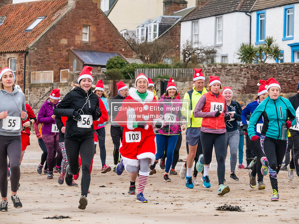 Pictured: Santa Beach Run on the scenic East Lothian coast. This new event is aimed at athletes, casual runners and families. It is hosted by Project Trust with proceeds enabling local school leavers to spend a year volunteering in India/Honduras to teach at a school with few teaching materials. The adults set off across West Bay beach in the 4km and 10km races. 15 December 2018  <br /> <br /> Sally Anderson | EdinburghElitemedia.co.uk