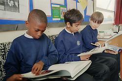 Secondary school boys reading in classroom,