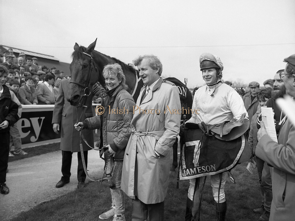 """Irish Grand National At Fairyhouse.  (R54)..1987..20.04.1987..04.20.1987..20th April 1987..The Easter Racing Festival at Fairyhouse included the running of the Jameson sponsored Irish Grand National. Another featured race was the Jameson Gold Cup which was also run on Easter Monday...Image shows Stablegirl,Owner and Winning jockey posing for pictures with the winning horse """"Brittany Boy""""in the winner's enclosure, Jameson's, Irish, Whiskey, jameson,"""
