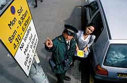 Traffic warden showing motorist restricted parking sign, London UK