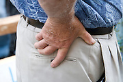 close up of elderly person with his hands on his hip