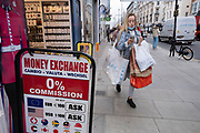 Youngwoman laden with shopping bags including Primark bags as the national lockdown ends and the new three tier system of local coronavirus restrictions begins, shoppers head out to Oxford Street to catch up on shopping as non-essential shops are allowed to reopen on 2nd December 2020 in London, United Kingdom. Many shoppers wear face masks outside on the street as a precaution as there are so many people around.