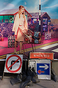Roadworks signs below a fashion poster featuring a young woman in a utopian fantasy about to cross a road. In a scene of retail paradise that features the model wheeling a shopping trolley, we also see a dystopian reality of the everyday city, the abandoned traffic signs leaning against this poster for the womens' retailer Oasis. A No Right-Turn and a Priority sign have been left on the ground, perfectly in context with the message above.