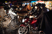 Bikes, motorcycles, pedestrians and cars crowd an intersection at dark during monsoon rain on May 10, 2008, in Kathmandu, Nepal. (David Stubbs / Aurora)