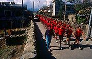 Young Nepali boys in army red march though a Pokhara street after being recruited for the Gurkha Regiment.  Trying for places in the Gurkha Regiment is part of a tough endurance series to find physically perfect specimens for British army infantry training. They will need to perform 25 straight-kneed sit-ups at a 45° slant both within 60 seconds to pass. 60,000 boys aged between 17-22 (or 25 for those educated enough to become clerks or communications specialists) report to designated recruiting stations in the hills each November, most living from altitudes ranging from 4,000-12,000 feet. After initial selection, 7,000 are accepted for further tests from which 700 are sent down here to Pokhara. Only 160 of the best boys succeed in the journey to the UK. The Gurkhas have been supplying youth for the British army since the Indian Mutiny of 1857.