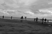 Men play football on a beach in Monrovia, Liberia.