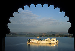 Asia, India, Rajasthan, Udaipur, Lake Palace Hotel and Pichola Lake viewed through arch.  This summer palace for the city's rulers was built in 1746.