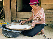 A Laoseng minority woman prepares rice for cooking outside her home in the remote and roadless village of Ban Phouxoum, Phongsaly province, Lao PDR. Ban Phouxoum is situated along the Nam Ou river (a tributary of the Mekong) and has been temporarily relocated due to the construction of the Nam Ou Cascade Hydropower Project Dam 6. The Nam Ou river connects small riverside villages and provides the rural population with food for fishing. But this river and others like it, that are the lifeline of rural communities and local economies are being blocked, diverted and decimated by dams. The Lao government hopes to transform the country into 'the battery of Southeast Asia' by exporting the power to Thailand and Vietnam.