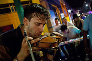 Young local band New Thousand with rapper Ray Wimley busking, playing in the street on Frenchman Street, with a young crowd loving the vibes and dancing, New Orleans, Louisiana, USA.