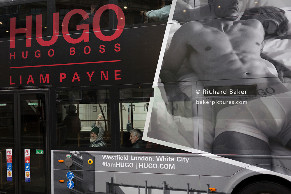 A passenger looks out the window of a London bus beneath a large ad for the menswear brand Hugo Boss and their male model, Liam Payne, on 12th November 2019, in London, England.