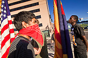 """22 OCTOBER 2011 - PHOENIX, AZ:    Occupy Phoenix protesters wait to cross a street during a march through Phoenix Saturday. The demonstrations at Occupy Phoenix, AZ, entered their second week Saturday. About 50 people are staying in Cesar Chavez Plaza, in the heart of downtown. The crowd grows in the evening and on weekends. Protesters have coordinated their actions with police and have gotten permission from the city to set up shade shelters and sleep in the park, but without tents or sleeping bags, which is considered """"urban camping,"""" instead protesters are sleeping on the sidewalk.    PHOTO BY JACK KURTZ"""
