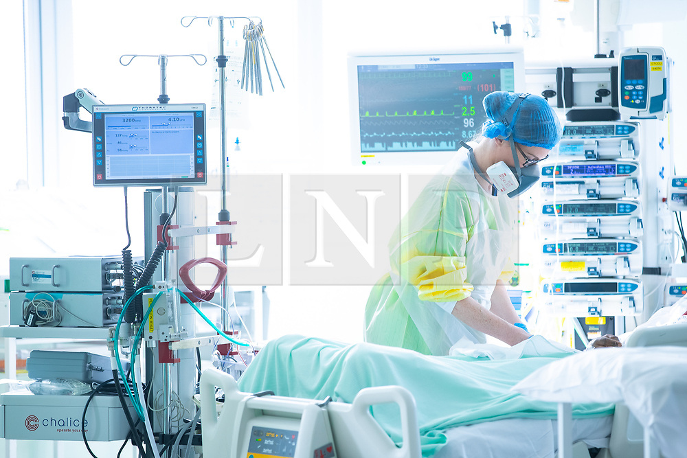"""© Licensed to London News Pictures . 11/02/2021. Wythenshawe , UK . Care is given to a patient connected to an """" ECMO """" device , inside Wythenshawe Hospital's Zone 3 Ward , where Covid positive patients suffering more severe effects of Coronavirus are treated with ECMO - ExtraCorporeal Membrane Oxygenation . ECMO provides cardiac and respiratory support to patients whose heart and lungs are unable to provide sufficient gas exchange . Photo credit : Joel Goodman/LNP"""