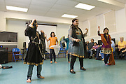 Student dancers Preeti Tanwani, 8, left, Arika Diwedi, 10, center, Kavya Nair, 10, dancer Vindhya Katta, and Shloka Nair, 9, right, demonstrate Nachale: The Bollywood Dance Workout with  center, and (not shown)  and  during the English Conversation Club: Dance and Dialogue event Saturday April 9, 2011 at the Iroquois Branch of the Louisville Free Public Library in Louisville, Ky. Henna and Bindi followed the Bollywood dance lesson, and then volunteers were paired with English language learners to work on conversation skills. (Photo by Brian Bohannon)