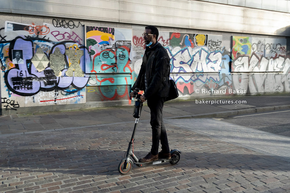 Warring a face covering on his chin, a commuter rides an eScooter past the graffiti on the exterior of a former office property in during the third lockdown of the Coronavirus pandemic, on 26th February 2021, in London, England.