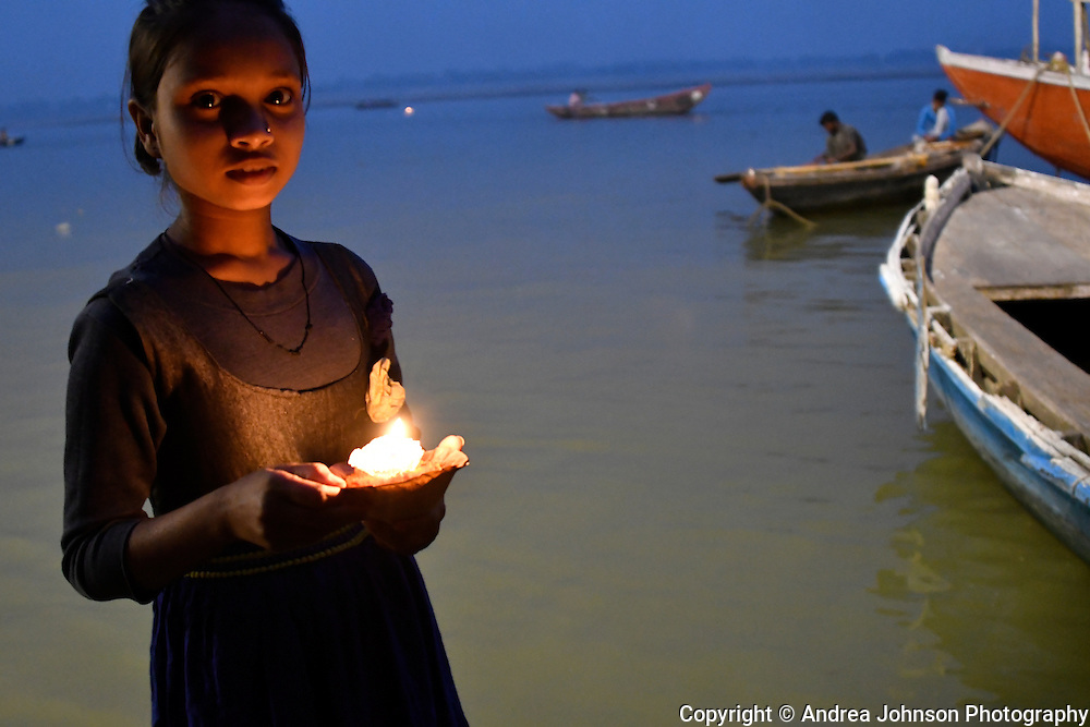 Hindu girl selling small candles inside a cup of leaves and flowers. Every dawn and dusk thousands of pilgrims travel to the Ganges and perform the Ganga Aarti ceremony; making a wish, lighting a candle, and setting it afloat on the river, Varanasi, India