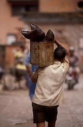 KATHMANDU, NEPAL - OCTOBER 1992 - A man carries a can full of animal hooves through the streets of Kathmandu. (PHOTO © JOCK FISTICK)