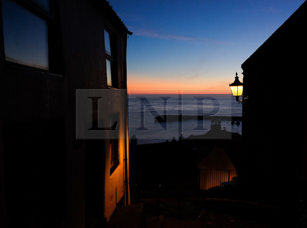 © Licensed to London News Pictures.02/10/15<br /> Staithes, UK. <br /> <br /> Dawn breaks over houses in the North Yorkshire village of Staithes on the east coast as the warm autumn weather continues.<br /> <br /> Photo credit : Ian Forsyth/LNP