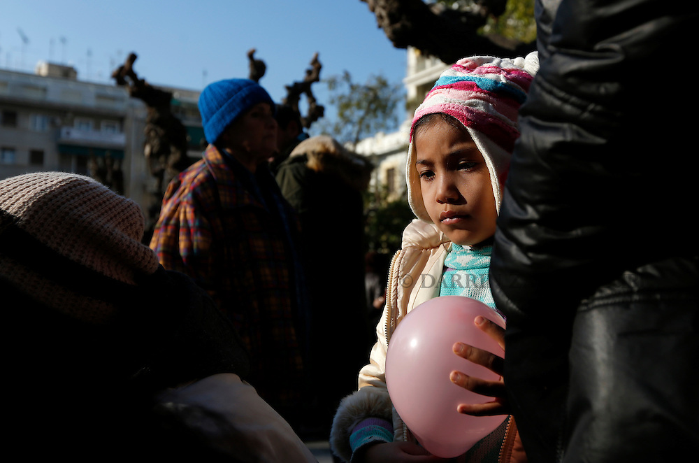 A migrant child holds a balloon while listening to adults talk in Victoria Square in central Athens, Greece, January 27, 2016. <br /> Photo: Darrin Zammit Lupi