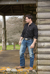 man standing on a rustic cabin porch