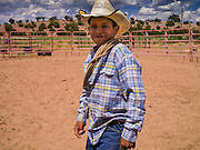 "13 JULY 2012 - FT DEFIANCE, AZ: A boy walks through the arena during a horsemanship clinic at the 23rd annual Navajo Nation Camp Meeting in Ft. Defiance, north of Window Rock, AZ, on the Navajo reservation. In addition to preaching and prayer, there are classes on horsemanship at the camp meeting. Preachers from across the Navajo Nation, and the western US, come to Navajo Nation Camp Meeting to preach an evangelical form of Christianity. Evangelical Christians make up a growing part of the reservation - there are now more than a hundred camp meetings and tent revivals on the reservation every year. The camp meeting in Ft. Defiance draws nearly 200 people each night of its six day run. Many of the attendees convert to evangelical Christianity from traditional Navajo beliefs, Catholicism or Mormonism. ""Camp meetings"" are a form of Protestant Christian religious services originating in Britain and once common in rural parts of the United States. People would travel a great distance to a particular site to camp out, listen to itinerant preachers, and pray. This suited the rural life, before cars and highways were common, because rural areas often lacked traditional churches.    PHOTO BY JACK KURTZ"