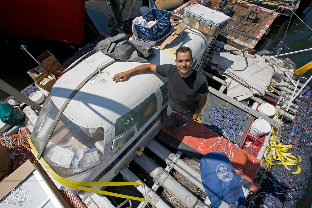 """Marcus Eriksen makes final preparations. in June of 2008, the raft named """"Junk""""  will sail 2,100 miles from Los Angeles to Hawaii to bring attention to the plastic marine debris (nicknamed the plastic soup) accumulating in the North Pacific Gyre. Designed by Dr. Marcus Eriksen and Joel Paschal, the raft is constructed from 15,000 plastic bottles, an airplane fuselage, discarded fishing nets and a solar generator. California, USA"""