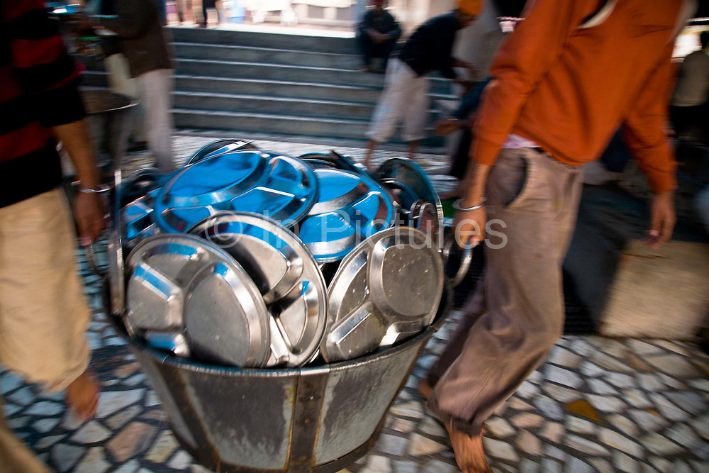 """Volunteers line up to wash the thousands of aluminium plates and cutlery that the pilgrims use each day on visiting their holiest of """"Gudwaras"""" the Golden Temple in Amritsar, Punjab, India."""