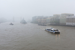 © Licensed to London News Pictures. 11/05/2016. LONDON, UK.  An early river commuter boat passes on the foggy River Thames as Tower Bridge and HMS Belfast behind are shrouded in fog, during foggy and wet weather this morning.  Photo credit: Vickie Flores/LNP
