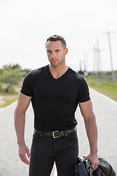rugged man in a black tee shirt standing on a road