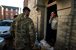 © Licensed to London News Pictures. 29/12/2015. York, UK. Royal Electrical and Mechanical Engineer soldiers  asking a resident on Huntington Road in York if he needs help following heavy flooding. Further rainfall is expected over coming days as Storm Frank approaches the east coast of the country. Photo credit: Ben Cawthra/LNP