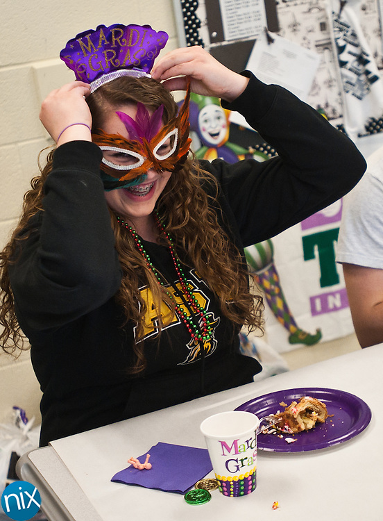 Hickory Ridge High School student Brenna Sullivan puts on her crown after being named queen during a Mardi Gras celebration in Amy Richard's French class at the school Tuesday morning. (Photo by James Nix)