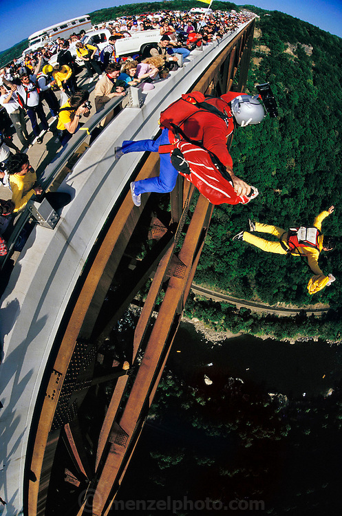 "Phil Smith and Randy BASE jumping from New River Gorge bridge, Bridge day, West Virginia, USA. BASE jumping is the sport of using a parachute to jump from fixed objects. ""BASE"" is an acronym that stands for the four categories of objects from which one can jump; (B)uilding, (A)ntenna (an uninhabited tower such as an aerial mast), (S)pan (a bridge, arch or dome), and (E)arth (a cliff or other natural formation). BASE jumping is much more dangerous than skydiving from aircraft and is currently regarded as a fringe extreme sport. -from Wikipedia ."