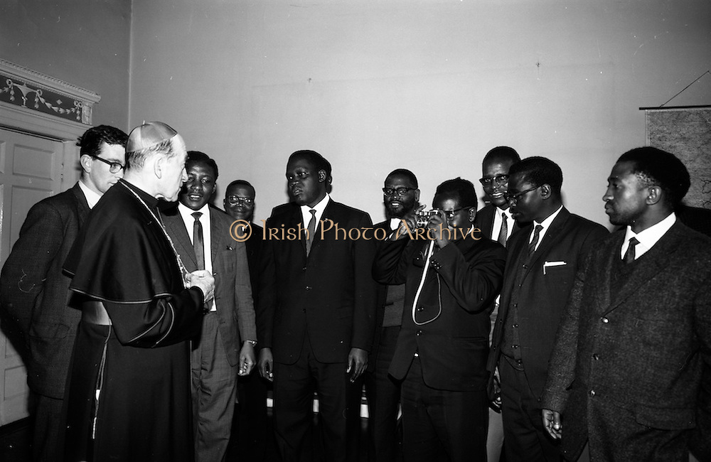 """06/05/1965<br /> 05/06/1965<br /> 06 May 1965<br /> African Students on a visit to Dublin. A group of African students of Catholic Sociology from Claver House, London, on an educational holiday to Ireland. The group stayed with Irish families under the auspices of """"Le Cheile"""" a group that promoted friendship and exchange of culture between Irish and overseas people. the students were entertained by His Grace, Most Rev. Dr. McQuaid, Archbishop of Dublin to a visit to the Dublin Institute of Catholic Sociology. Photo Shows Archbishop McQuaid chatting to the students while Fr. Stefan Haule (Tanzania) takes the opportunity to take a photograph."""